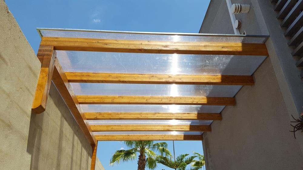 Pérgola cogida a pared y a fachada con techo de placas de policarbonato