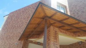 """Marquesina """"pasillo"""" de madera con techo de placas de tégola."""