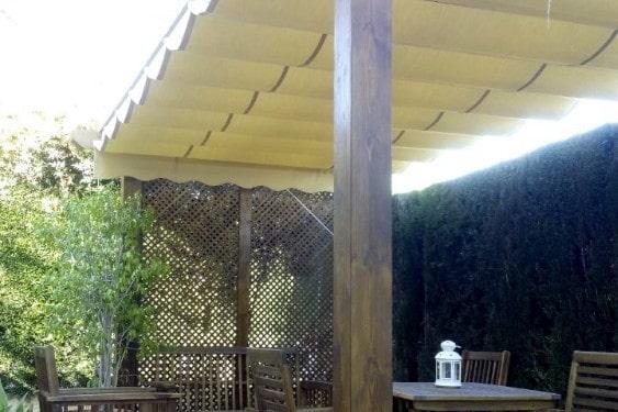 Pérgola de madera con toldo sobre las viguetas de madera