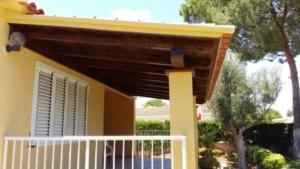 Porche de madera con columnas de obra, vista lateral de la terraza.