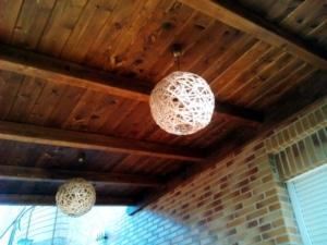 Lamparas de bolas de hilo, en un techo de un porche de madera