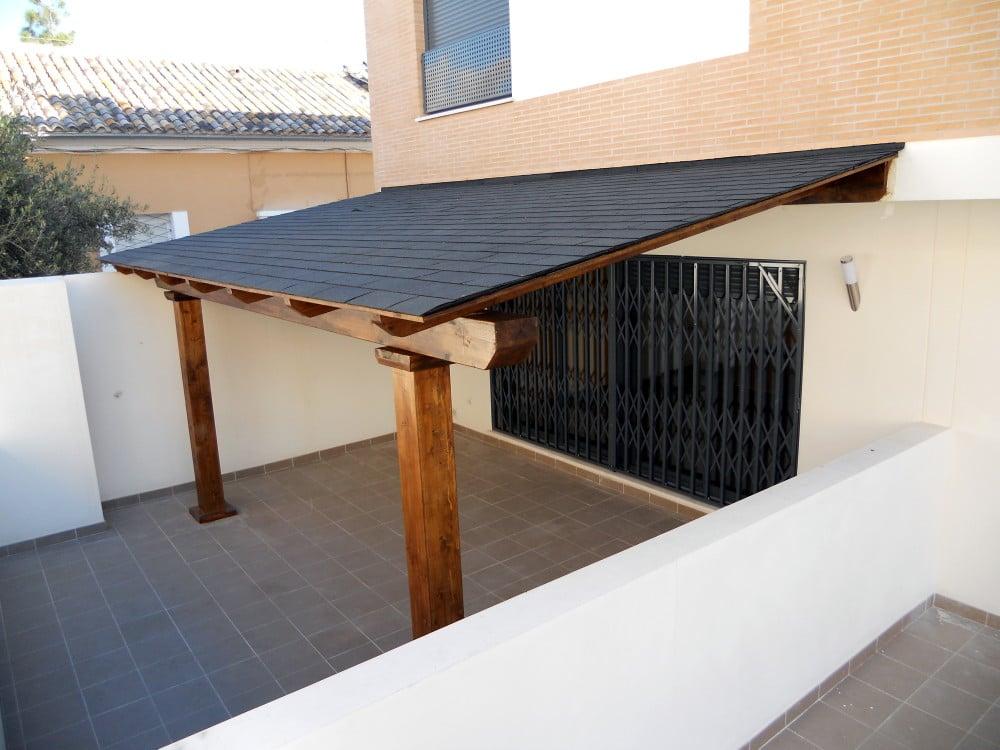 porche de madera con techo de placas de tgola negras