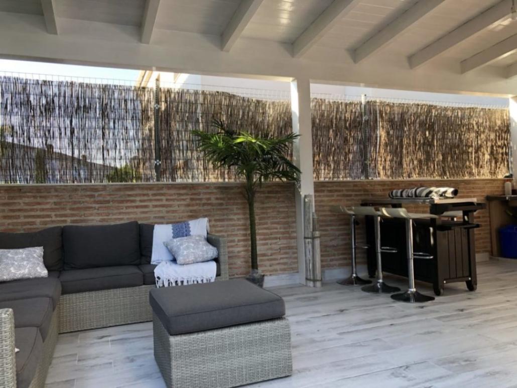 Interior porche de madera barnizado todo en blanco, techo machihembrado y estructura.